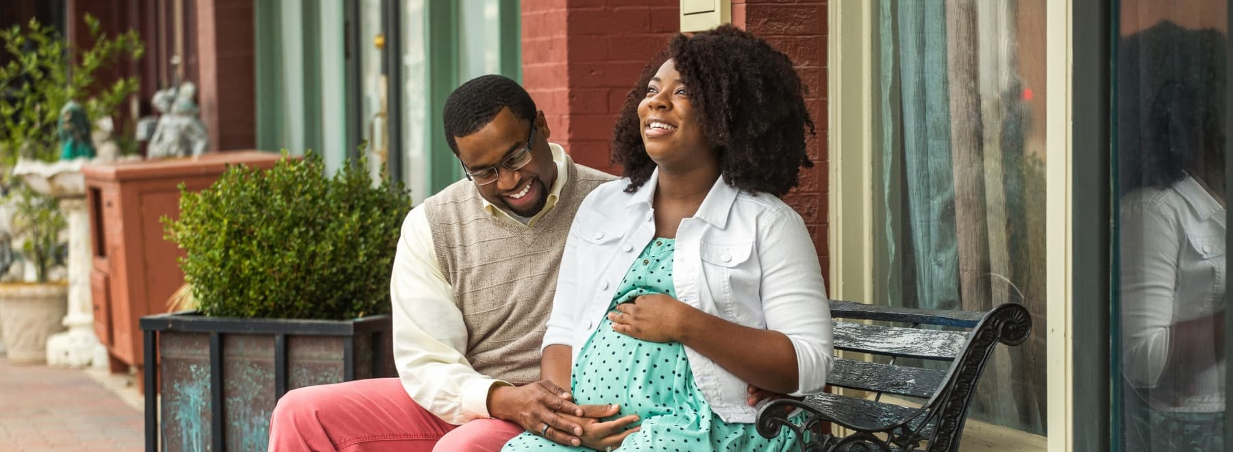Smiling man puts hand on pregnant woman's stomach while sitting on a bench