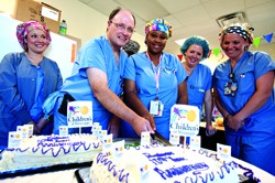 Dr. Edwin Harmon, second from right, professor of pediatric urology, and Vicki Rhymes, center, shift supervisor, cut the 10th anniversary cake while, from left, Shannon Furrer, RN, Angela Smith, surgical tech and Ashley Taylor, RN, look on.