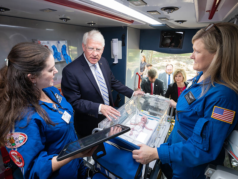 U.S. Sen. Roger Wicker learns about a specialized intensive care isolette from  transport nurse practitioner Casey Hall, left, and transport registered nurse April Davidson. The Mississippi Center for Emergency Services' deployable vehicles includes critical care transport for newborns.