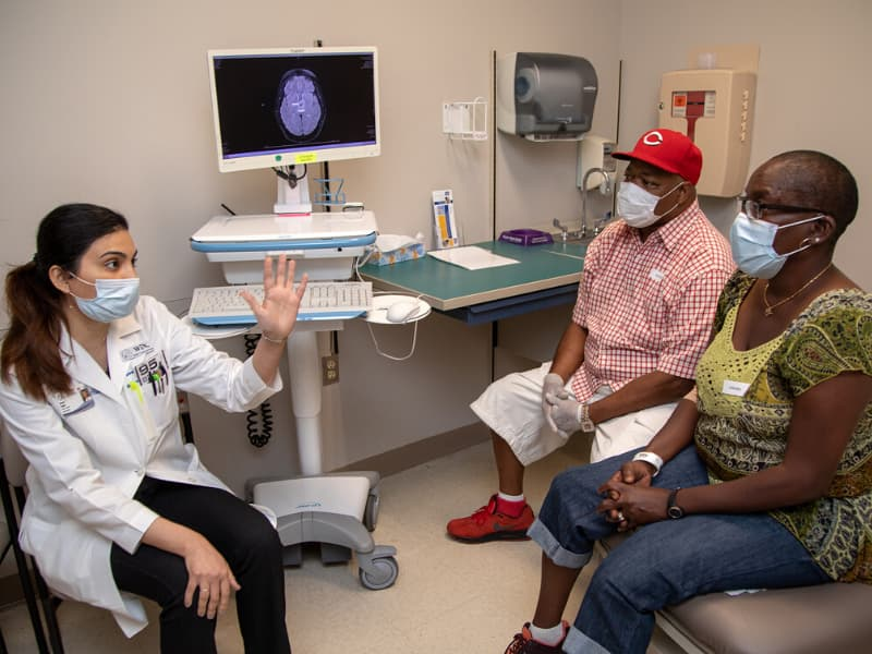 Dr. Nawal Shaikh, left, reviews am image with Marzina Jones and her husband, Steven. Marzina Jones has a rare brain tumor with a BRAF mutation so is receiving a medication that targets that mutation.