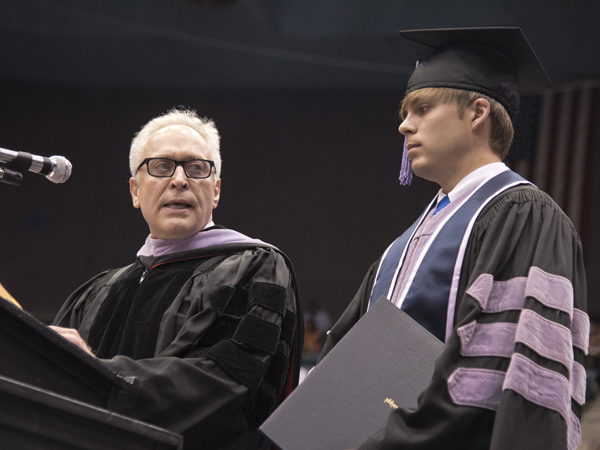 School of Dentistry Dean Gary Reeves gives the Wallace V. Mann Jr. Award to graduate Michael Cole Collier.