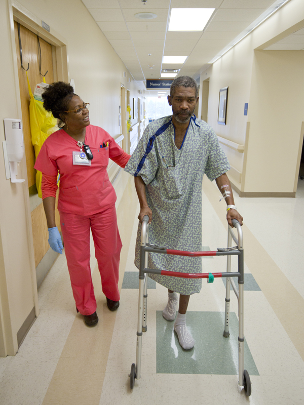 Jennifer Clay encourages patient Donald Dean of Shelby as he gains strength and gets back on his feet.