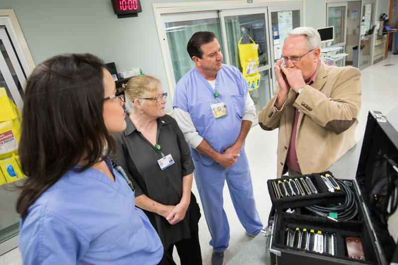 Former patient David Bowman, right, plays harmonica for CICU staff members, from left, Registered Nurse Presly Lowry, housekeeper Cynthia Gonzalez and Nurse Manager Don Horn during a return visit to the CICU.