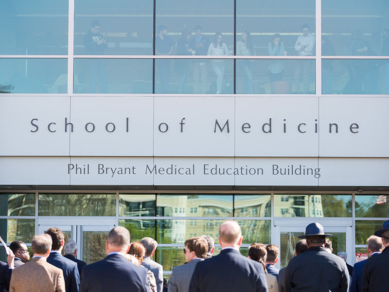 "As a chilly wind whipped the crowd gathered outside for the unveiling of the Phil Bryant Medical Education Building, Gov. Bryant called attention to dozens of medical students who lined five stories of windows inside the building. ""They seem somewhat tired and stressed,"" he joked."