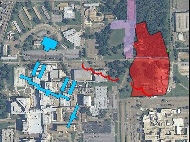 A modern-day aerial view of the Medical Center campus is enhanced with a historic overlay of the asylum's main buildings (in blue) and the cemetery boundary (in red).