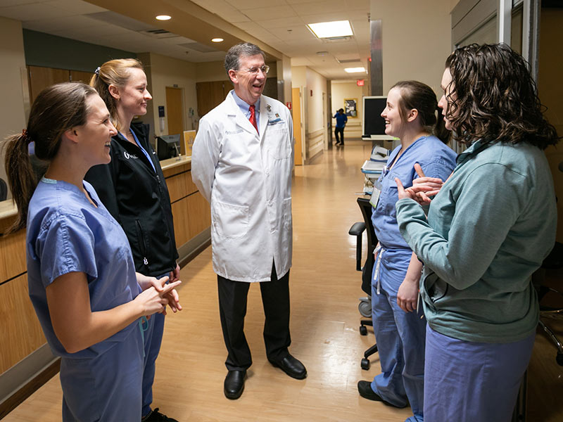 Doctor talking to group of medical students in hallway.