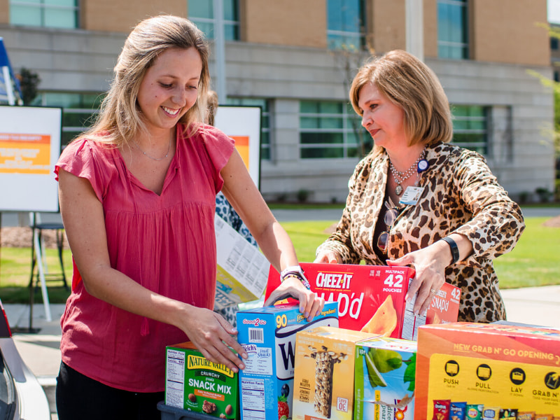 Olivia Woodward, left, and her mom, Dr. LouAnn Woodward, vice chancellor for health affairs and dean of the School of Medicine, hand off donations for COVID-19 relief at the Medical Center at a dropoff station in front of the School of Medicine.