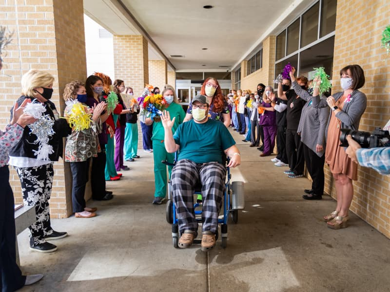 Front-line caregivers at the Medical Center cheer on Raleigh resident Timothy Hudson, the 1,000th patient with COVID treated at UMMC, as he departs following a one-week stay.