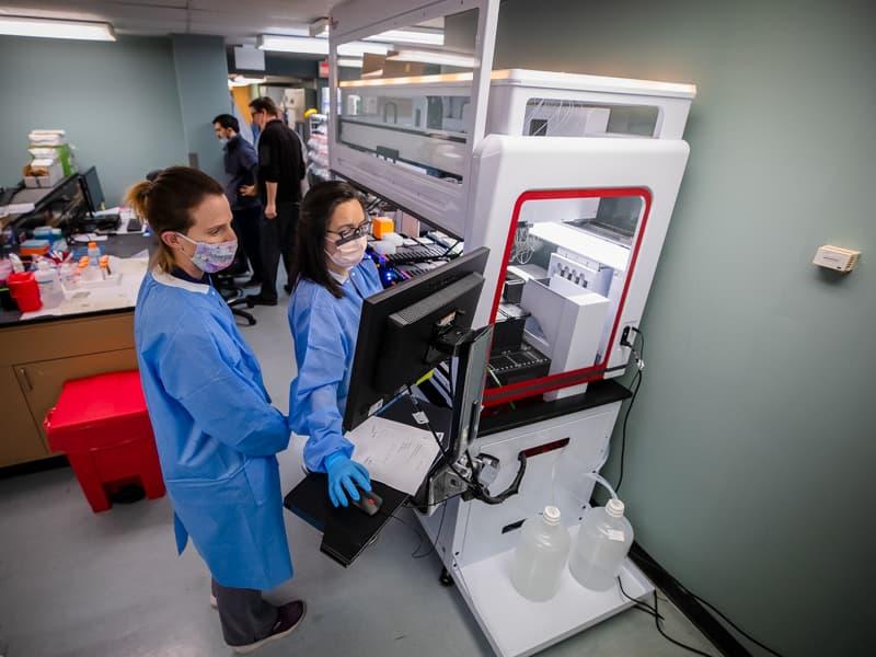 Les technologues médicaux enregistrés Jackie Starrett, à gauche, et Sara Kemp observent la progression des échantillons COVID-19 sur le nouveau robot Biomek i7 dans le laboratoire de pathologie moléculaire.