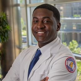 Male radiologic sciences student smiles while posing in the school of health related professions building.