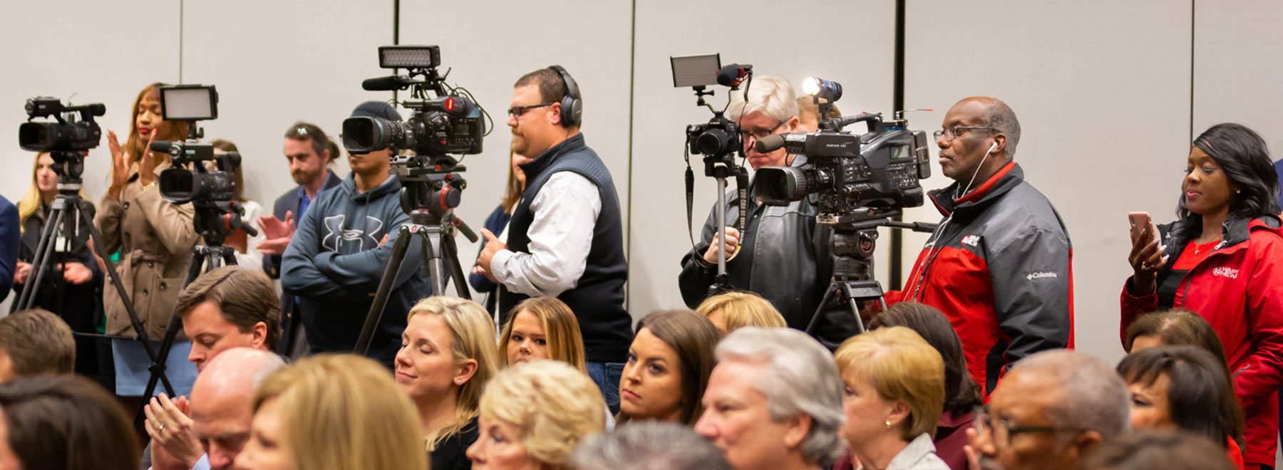 Video cameras in the back of the room during an event.