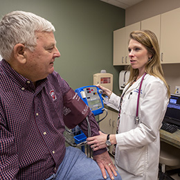 Physician checks a man's blood pressure