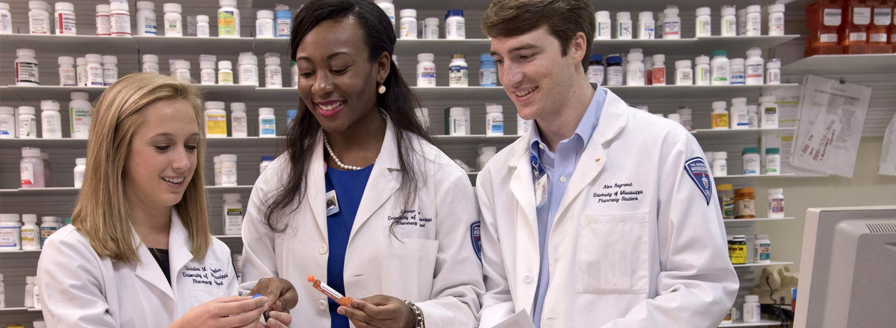 Three School of Pharmacy students in a pharmacy setting