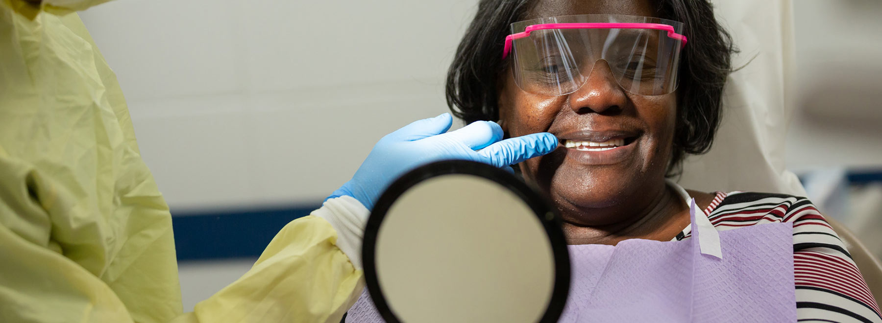 Women looks at new dentures in hand mirror