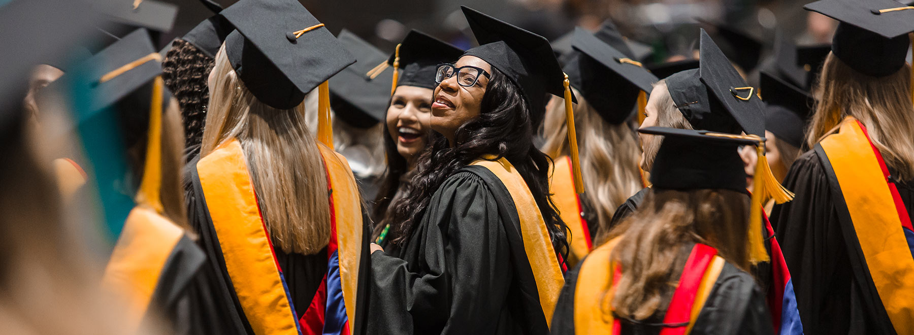 Woman in cap and gown during commencement.