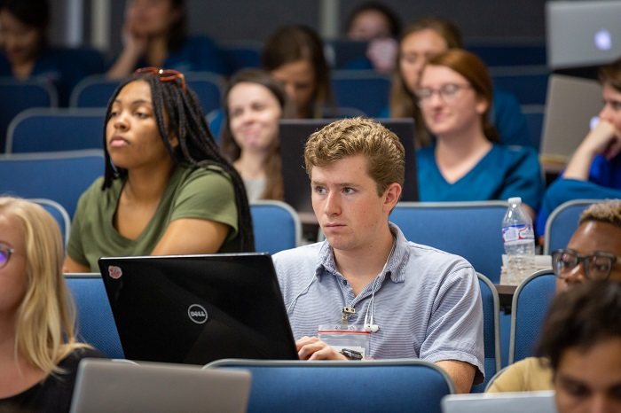 Students listen to lecture by Tom Adair