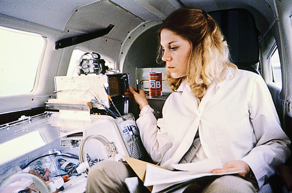 Transport nurse Kay Sucier watches an infant from her seat aboard a fixed-wing aircraft while enroute to Children's Hospital. Aircraft often were used in the early days of the transport program.