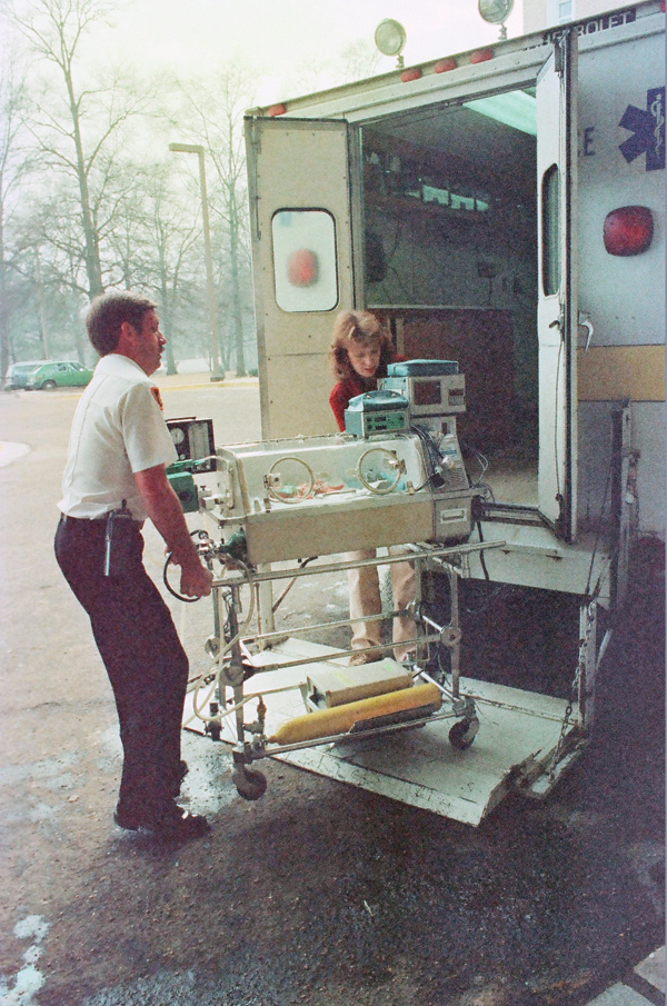 UMMC Nurse Nancy Park helps Jackson Fire Department driver Pat Kelly move an infant from the Neonatal Cradle into the Children's Hospital in 1983.