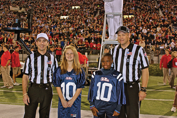 "Jacob stands at midfield during a 2013 Ole Miss football game as a ""kid co-captain."""