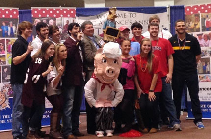 D.P.T. students celebrate their victory with Dr. Fine Swine, Taste of the U mascot.