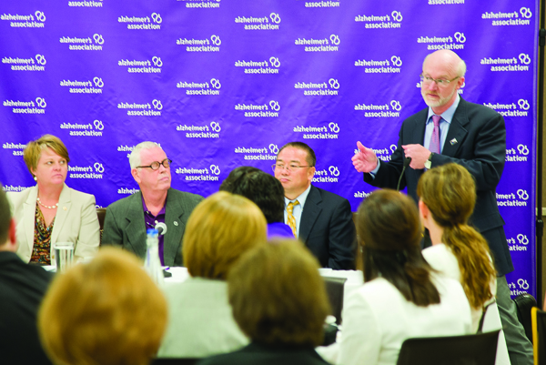 UMMC's Dr. Tom Mosley, far right, standing, makes a point during the Alzheimer's Research Round Table Luncheon held Aug. 12 in Jackson. Panelists include, from left, Patty Dunn, executive director of the Alzheimer's Association/Mississippi Chapter, which co-hosted the event with the Greater Jackson Chamber of Commerce Partnership; Mike Quayle, a Jackson businessman diagnosed with Alzheimer's; Dr. Junming Wang, UMMC associate professor of research and a member of the research team for the Memory Impairment Neurodegenerative Dementia Research (MIND) Center; and Mosley, MIND Center director and professor of geriatric medicine. Among the developments reviewed by Mosley and Wang were the discovery of a molecule that may become a biomarker for Alzheimer's and advances in brain imaging.