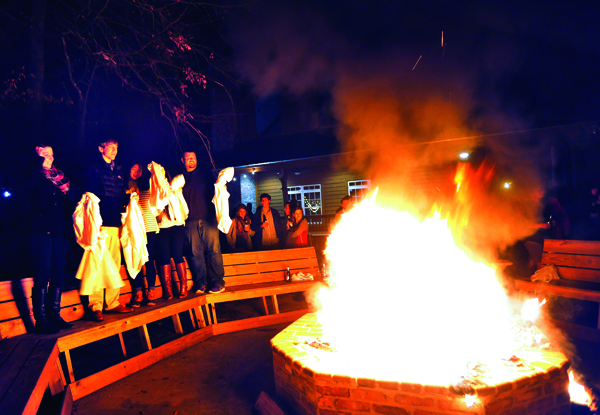 First-year medical students, from left, Kate Garner, Colton Lee, Cathy Chen, Kim Zachow and Brent Necaise join their fellow classmates in the coat-burning ritual, an annual rite of passage for M1s celebrating the end of Gross Anatomy by chucking their lab coats into a roaring fire. The ceremony was part of a semester-ending party held Dec. 12 at McClain Lodge in Rankin County. These five students, along with Rachel Sharp, worked together at the lab's Table 25.