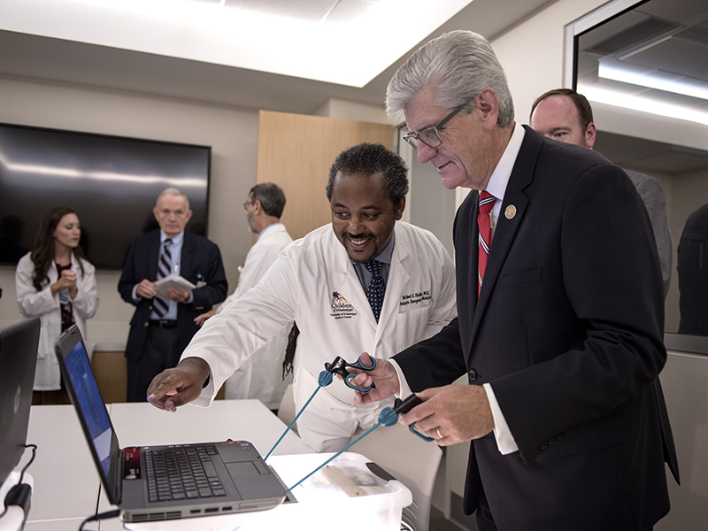 Dr. Michael Holder, left, associate professor of pediatric emergency medicine and executive director of the Office of Interprofessional Simulation, Training, Assessment, Research and Safety, shows Gov. Phil Bryant how to play a game that simulates performance of surgery.