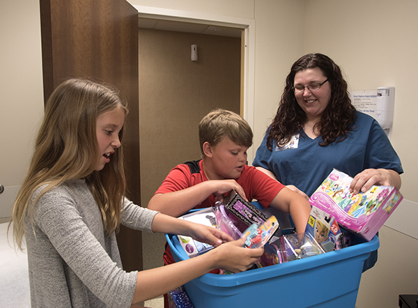Amber Taylor, right, a family medicine nurse, helps twins Jordyn and Justice Burgemaster of Madison choose a toy from a box.