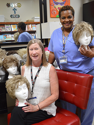 Ruth Cummins, UMMC assistant director for media relations, seated, and her siblings donated their mother's wigs and many stands to the Patient Resource Center. Resource Center manager Janice Johnson helped set them up.