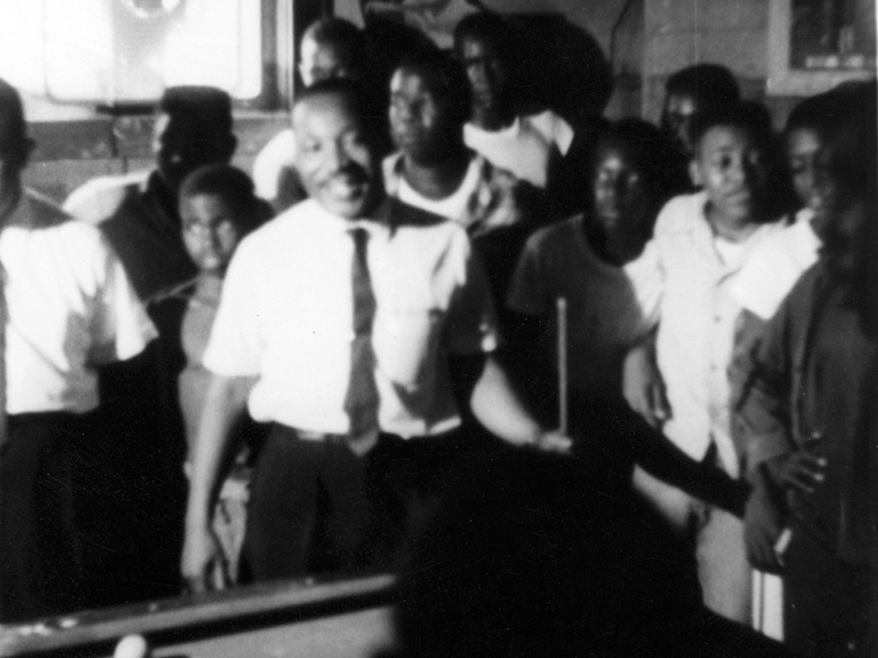 "The Rev. Martin Luther King Jr. is surrounded by admirers in a Neshoba County pool hall, where he spoke about registering to vote and supporting the Mississippi Freedom Democratic Party, July 1964. A sign in the upper left corner of the photo says, ""No Bad Language."" (Photo used with the permission of the Rev. Ed King, University Press of Mississippi and the Mississippi Department of Archives and History)"