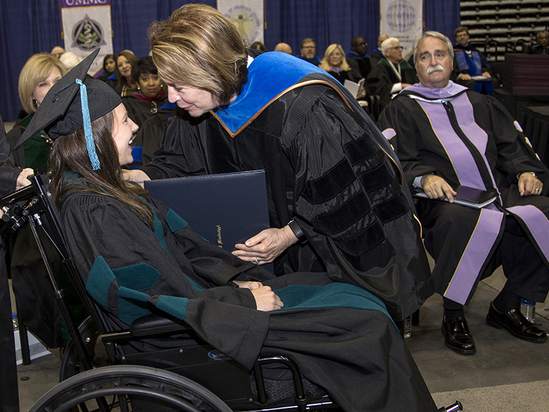 A smiling Green receives her diploma from Dr. Jessica Bailey, dean of SHRP, while other school deans look on during UMMC's Commencement May 25.