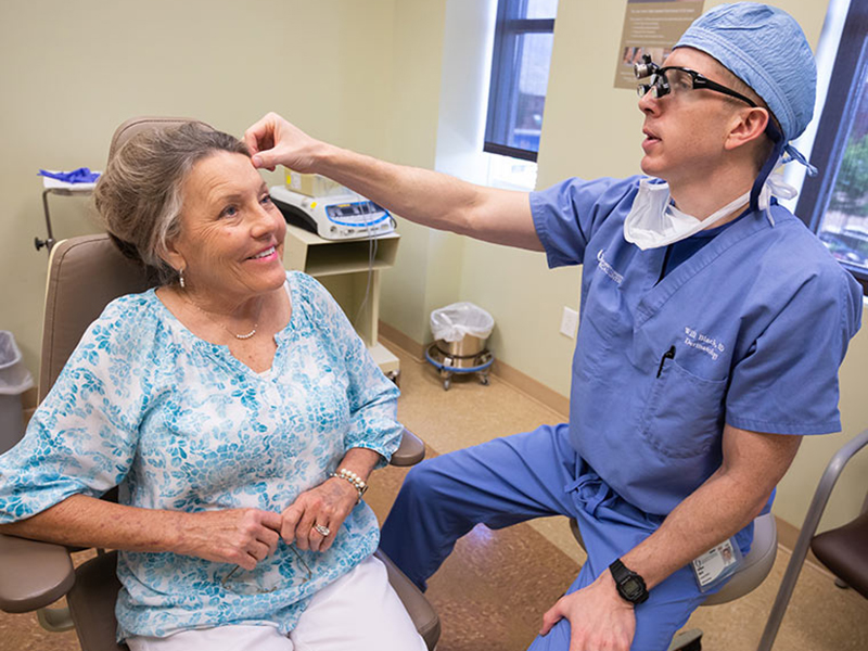 Dr. William Black, right, examines Linda Puckett's forehead. Black used Mohs surgery to remove a melanoma from the area.