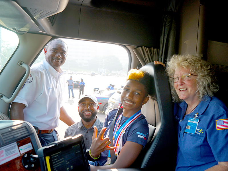 Smiling from inside the cab of a Walmart 18-wheeler is Mississippi's Children's Miracle Network Hospitals Champion KJ Fields, flanked by driver Ricky Sharp, left, his father Kelvin Fields and driver Devan Griffin.
