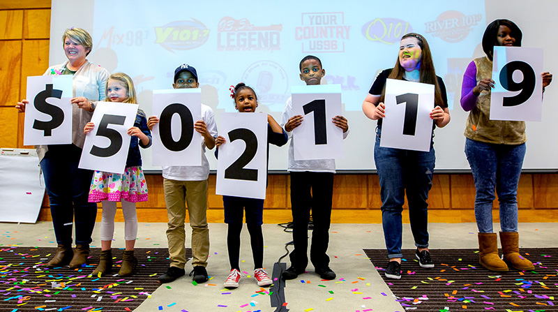 Showing the amount raised during the 18th Mississippi Miracles Radiothon are, from left, Tara Cumberland and her daughter, Sybil, De'Nahri Middleton, De'Niylah Middleton, De'Nahjae Middleton, Hannah Dunaway and Decimbra Middleton.