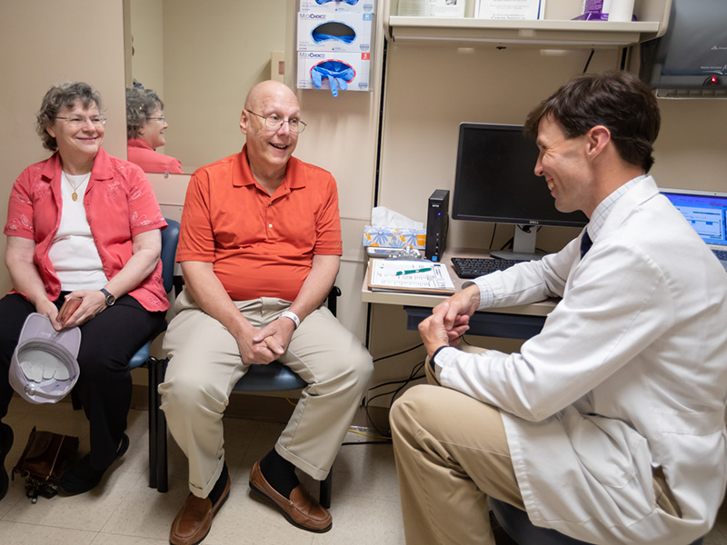 Dr. Clark Henegan, assistant professor of hematology and oncology, talks to patient Paul Gay and his wife, Dr. Hannah Gay, about results of a recent prostate cancer PET/CT scan.