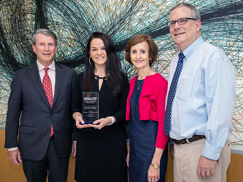 Dr. Chelsea S. Mockbee, second from left, receives the Caldwell Award from Dr. Eric A. McVey, left, chairman of the MACM Board of Directors and Dr. Gerry Ann Houston, MACM medical director, while Dr. Robert T. Brodell, UMMC professor and chair of dermatology, observes.