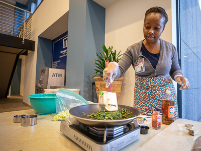 Fiona Lewis, a dietitian in the Department of Preventive Medicine, cooks kale and squash dishes at the Office of Wellbeing's fair at the Clinton Billing Office.