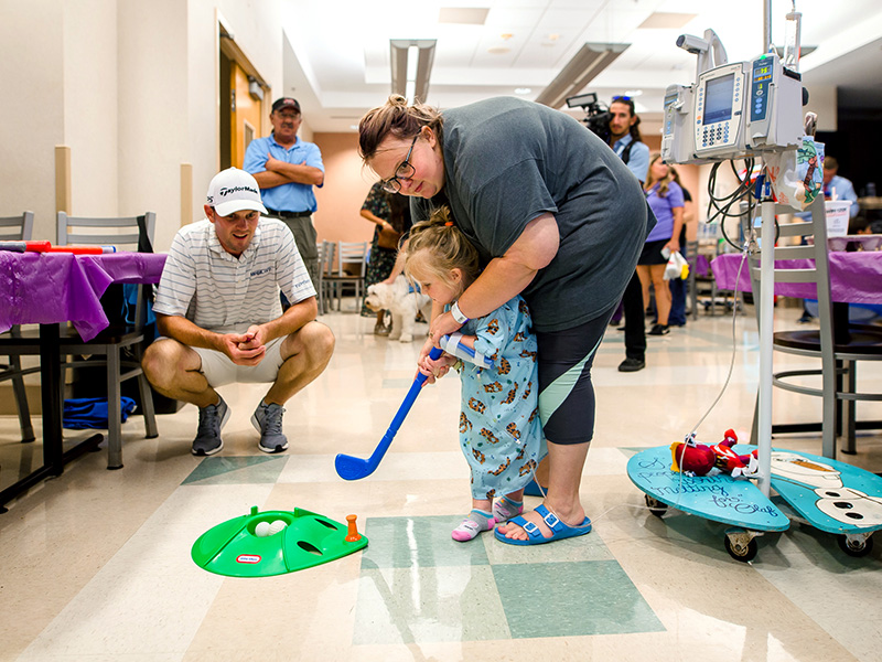 Sanderson Farms Championship golfer Wes Roach gives golfing tips to Children's of Mississippi patient Ruby Kate Greer and her mom, Kailyn, of Hermanville during a 2019 visit to the children's hospital.