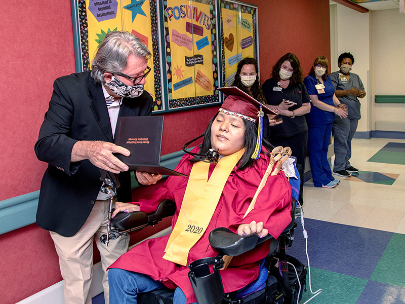 Teacher Ron Johnson from Choctaw Central High shows Deontay Isaac her high school diploma.