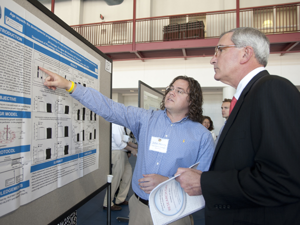 John Henry Dasinger, left, UMMC graduate assistant, explains his research project to Dr. Dzielak during the School of Graduate Studies in the Health Science Research Day.