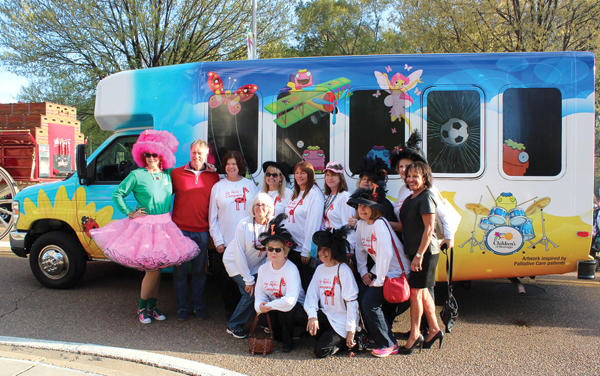 Proceeds from the 2014 Fondren's Zippity Doo Dah Weekend helped Friends purchase a new van for Batson's palliative care patients. Jill Conner Browne, left and Braveheart screenwriter Randall Wallace, second from left, along with Queens Classymates members present the van to Ray, right.