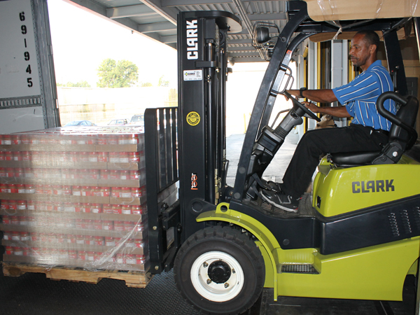 Mike Roche, warehouse manager at the Mississippi Food Network in Jackson, uses a forklift to transport peanut butter to waiting trucks for distribution.