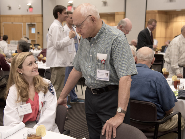 Hannah Green, left, a medical student volunteer, visits with Dr. Frazier Ward, Class of '65.