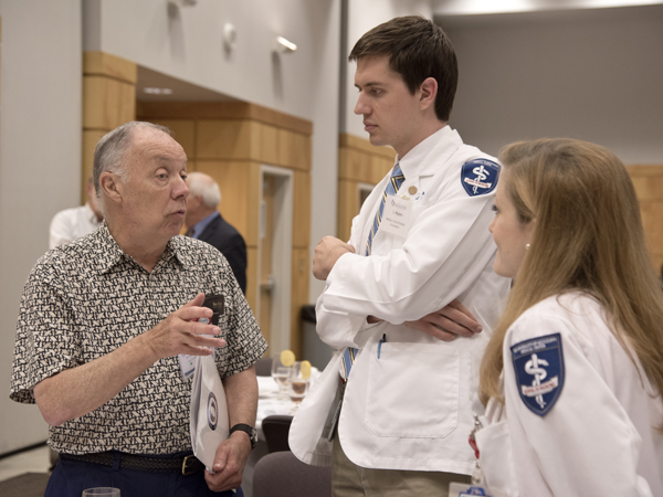 Dr. Gary Nye, left, Class of '65, makes a point with fourth-year medical student Lance Majors, center, and Hannah Greene, an M3.