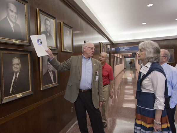 Pointing to portraits of past UMMC leaders, Dr. James Keeton, left, enlightens a group of alumni and spouses during a tour of the Medical Center. Among those looking on are Dr. Charles B. Itzig Jr., center, and Mary Abraham, right, wife of Dr. Ralph Ellis Abraham.