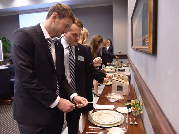 Miles Backstrom, left, and Brooks Jackson go over the proper placement of plates and silverware during their meeting November 10 at the Norman C. Nelson Student Union.