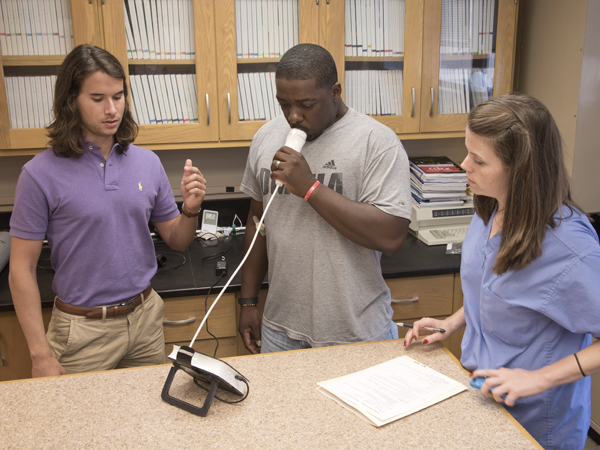Second-year School of Medicine students Evan Ciarloni (left) and Jillian Merica give an asthma breathing test to Charley Williams, who copes with asthma.