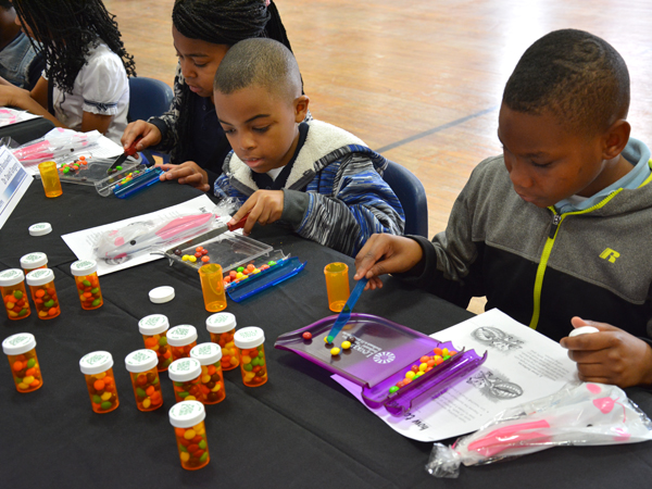 Zian Sims, right, Brian McCray and Desiree Strong learn the importance of pharmacy while participating in a mock pill-counting demonstration.