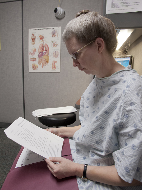 Bynum reads over an evaluation form used to gauge a student's aptitude for communicating with a patient and appraising a patient's condition.
