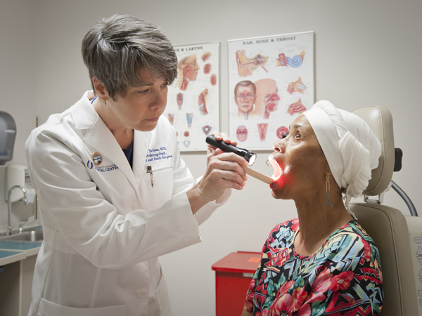 Dr. Lana Jackson, associate professor of otolaryngology and communicative science, examines the mouth of patient Bettye Lovelady during a Cancer Institute-sponsored oral cancer screening event.